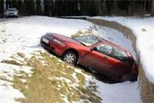 Car in snow in ditch